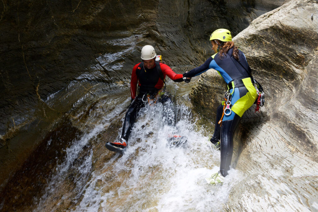 Couple having fun in a canal, practicing canyoning.