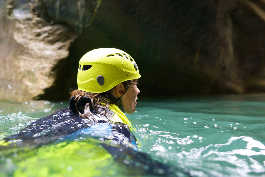 A woman swims in a canal while practicing canyoning.