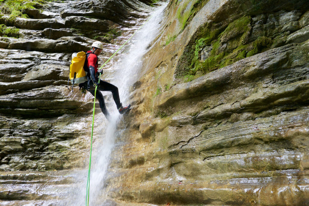 A man abseils a rope while practicing canyoning.