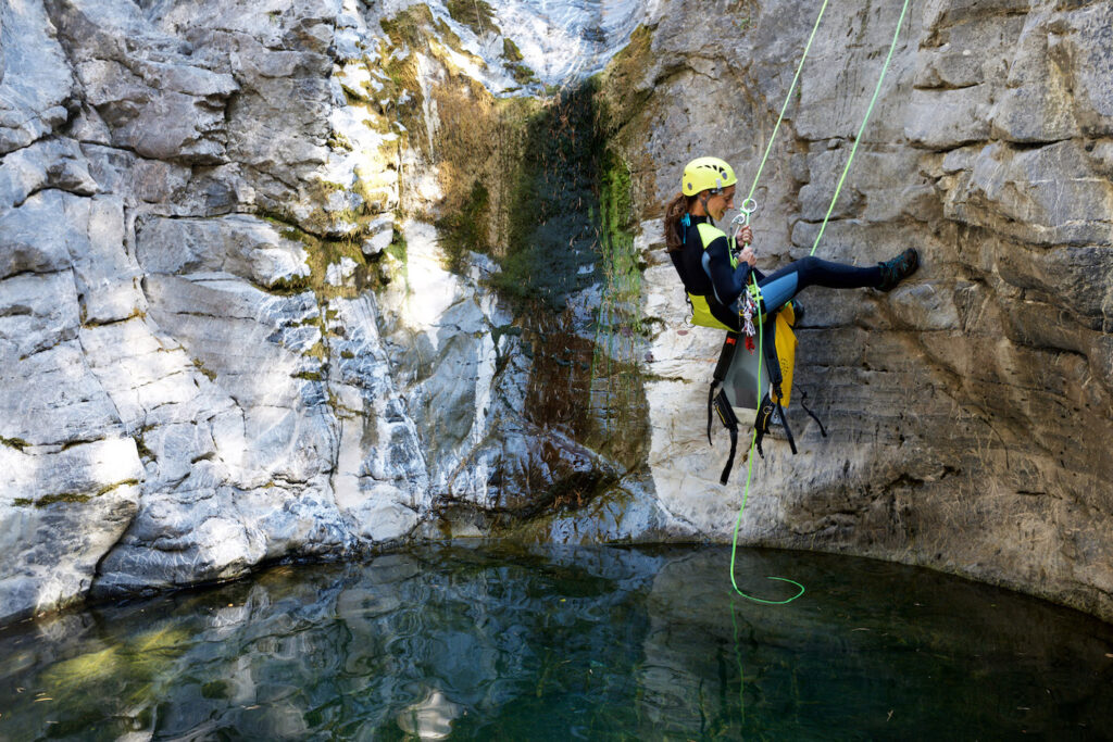 A woman abseils herself by canyoning.