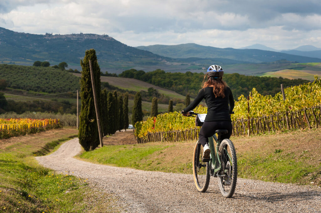 A woman pedaling, immersed in the Umbrian countryside, surrounded by a splendid vineyard.