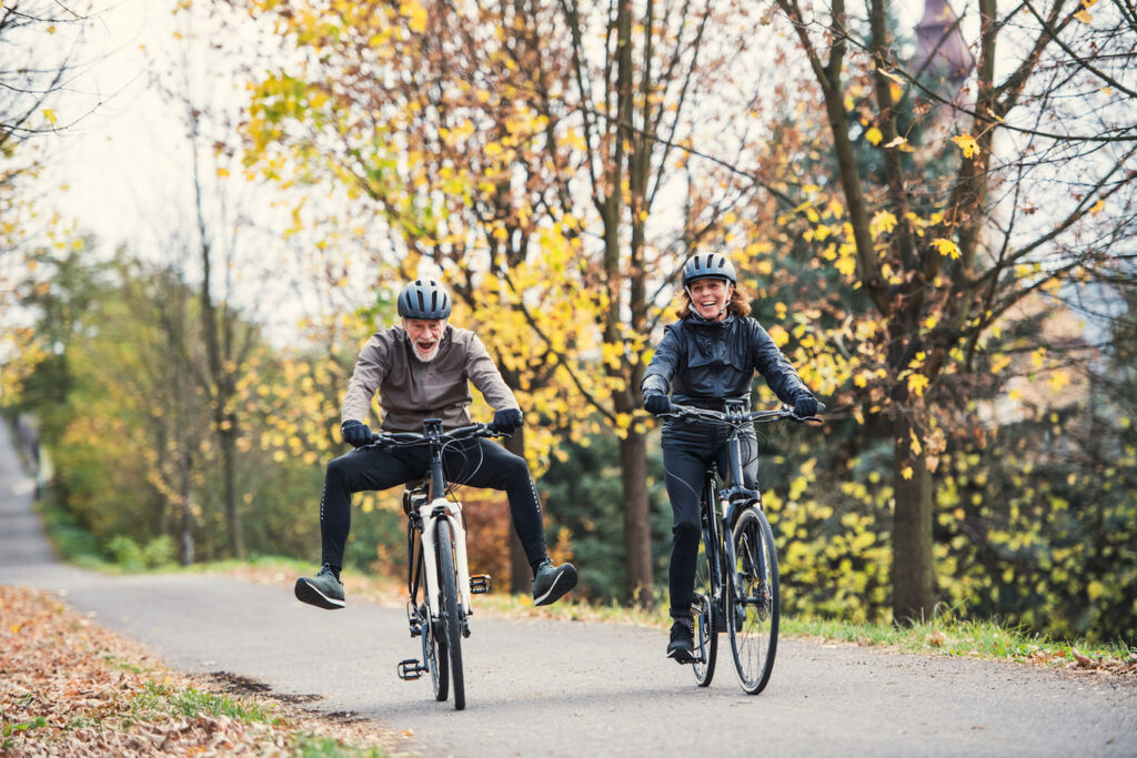 A couple is having fun with the ebikes, along a country road in Umbria.