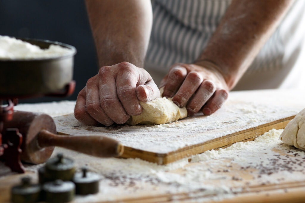 A chef kneads fresh pasta by hand.