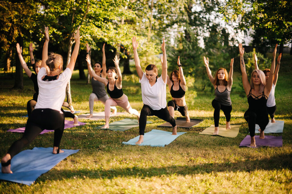 A group of women practice Pilates in the garden