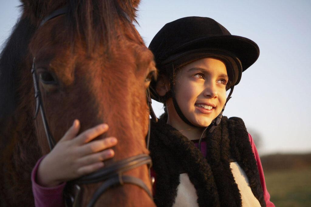 A little girl hugs her horse.