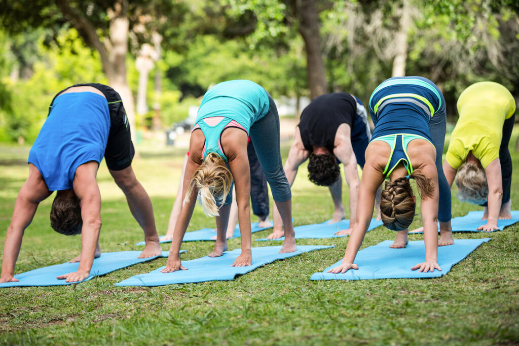A group of women practice Yoga in the garden